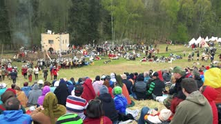 People sit in hill and observe a people in costumes in mediaeval battle