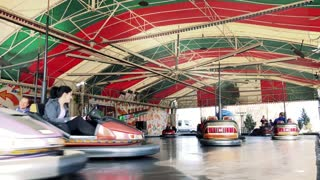 People sit in seats in small runabout and ride on track in funfair