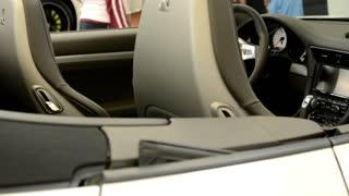 PRAGUE, CZECH REPUBLIC, CAR EXHIBITION - SEPTEMBER 27, 2014: dashboard, wheel,shift(gear) lever and seats - Porsche 911 Turbo - people on exhibition