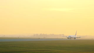 Slowmotion airplane goes on runway at sunset