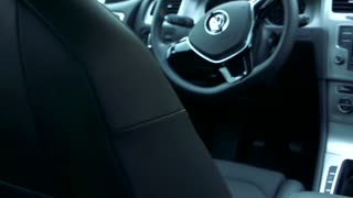 Slowmotion view on steering wheel, gear lever and technology in car.