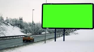 Snowy landscape and billboard at a road where go cars