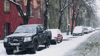 Snowy road with parked cars at heavy snowfall