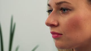 The profile of a young, beautiful female face while she works on a computer - closeup
