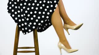 A 50s pin-up sits on a stool and swings her legs - closeup - white background