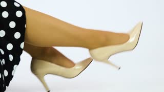 A 50s pin-up sits on the floor and swings her legs - closeup - white background