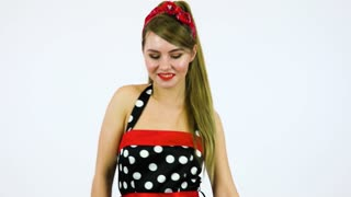 A beautiful 50s pin-up girl dances and smiles at the camera - white screen background