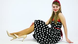 A beautiful 50s pin-up girl sits on the floor, smiles at the camera and moves in rhythm of music - white background