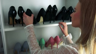 A beautiful blonde woman looks at high heel shoes on shelves