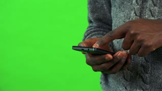 A black man works on a smartphone - closeup - green screen studio