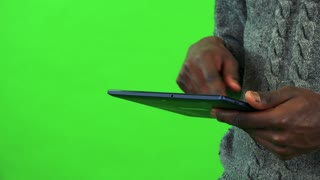 A black man works on a tablet - closeup - green screen studio