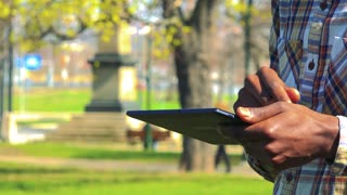 A black man works on a tablet in a park on a sunny day - closeup