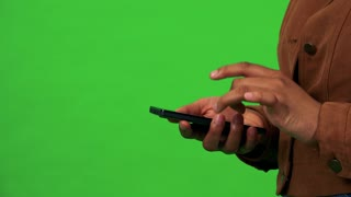 A black woman works on a smartphone - closeup - green screen studio