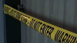 A closeup on a police tape across an apartment door