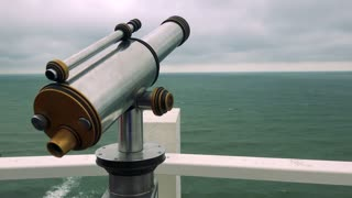 A coin telescope by a white rail with a view at a sea and the cloudy gray sky