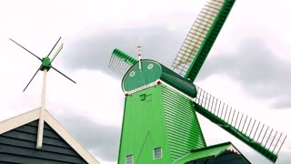 A green windmill and the top of a house from below, the vane spins in the wind, the cloudy gray sky in the background