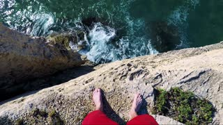 A man stands on the edge of a cliff by the sea - first person view
