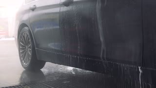 A man washes his dark gray car with a hose in a self-service car wash station - closeup on the bottom