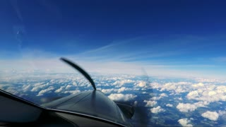 A private plane flies above the clouds - a view from the cockpit - spinning propeller