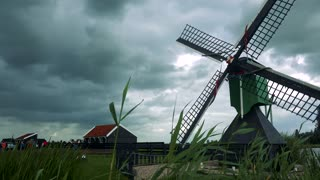 A vane of a black and green windmill spins fast in the wind, people, buildings and the cloudy gray sky in the background, stems of grass in the foreground