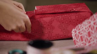 A woman wraps a gift in a Christmas paper on a couch - closeup - other presents and wrapping tools in the blurry foreground