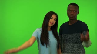 A young Asian woman and a young black man wave at the camera in a gesture of invitation - green screen studio