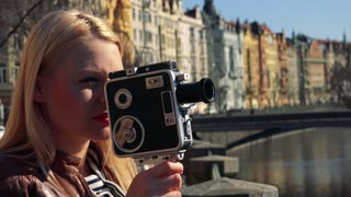 A young attractive woman shoots a video, then smiles at the camera - face closeup - a river and a bridge in an urban area in the blurry background