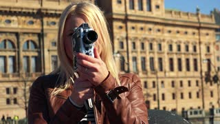 A young attractive woman shoots a video with a camera - closeup - an old building in the blurry background