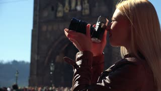 A young attractive woman takes photos with a camera - closeup from the side - people and a tower in the blurry background
