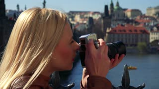 A young attractive woman takes photos with a camera - face closeup from the side - a river and a big quaint town in the blurry background
