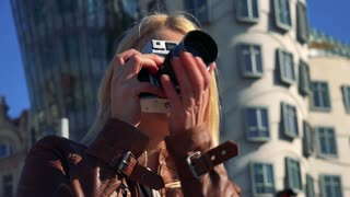 A young attractive woman takes pictures with a camera in an urban area - closeup from below - buildings in the blurry background