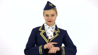 A young beautiful stewardess taps her watch at the camera and points a finger to the sky - white screen studio