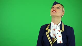 A young beautiful stewardess watches a plane fly by - green screen studio