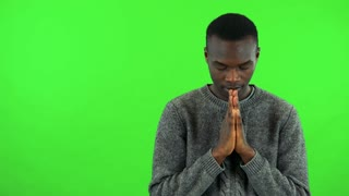 A young black man prays with hands clasped together - green screen studio