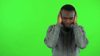 A young black man protects his ears from a loud sound - green screen studio