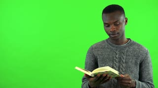 A young black man reads a book - green screen studio