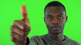A young black man shows a thumb up to the camera - closeup - green screen studio