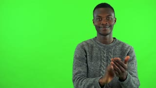 A young black man smiles at the camera and applauds - green screen studio