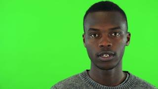 A young black man talks to the camera - face closeup - green screen studio
