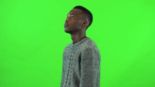 A young black man walks back and forth and thinks about something - green screen studio