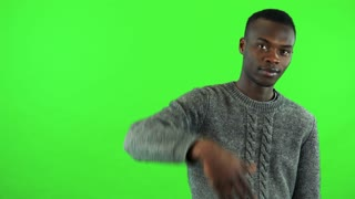 A young black man waves at the camera in a gesture of invitation - green screen studio