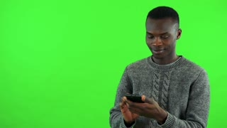 A young black man works on a smartphone with a smile - green screen studio