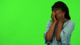 A young black woman cries with hands over her face - green screen studio