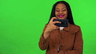 A young black woman takes pictures of something off the camera with a smartphone - green screen studio