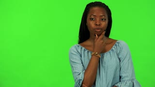 A young black woman thinks about something - green screen studio