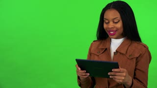 A young black woman works on a tablet with a smile - green screen studio
