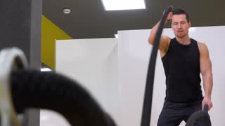 A young fit man trains with battle ropes in a gym