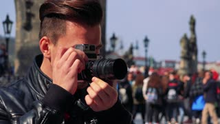 A young handsome man takes photos on a town square - face closeup - people in the blurry background