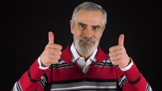 An elderly man smiles and shows a double thumb up to the camera - black screen studio