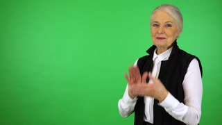 An elderly woman applauds and smiles at the camera - green screen studio